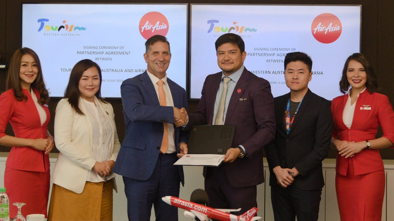 Photo Caption (L-R):-  Tourism Western Australia Country Manager for Singapore and Malaysia Ava Ang; Western Australia Tourism Minister Hon. Paul Papalia; AirAsia X Malaysia CEO Benyamin Ismail and AirAsia X Malaysia Marketing Manager Chia PinYu flanked by AirAsia Cabin Crew at the signing ceremony.