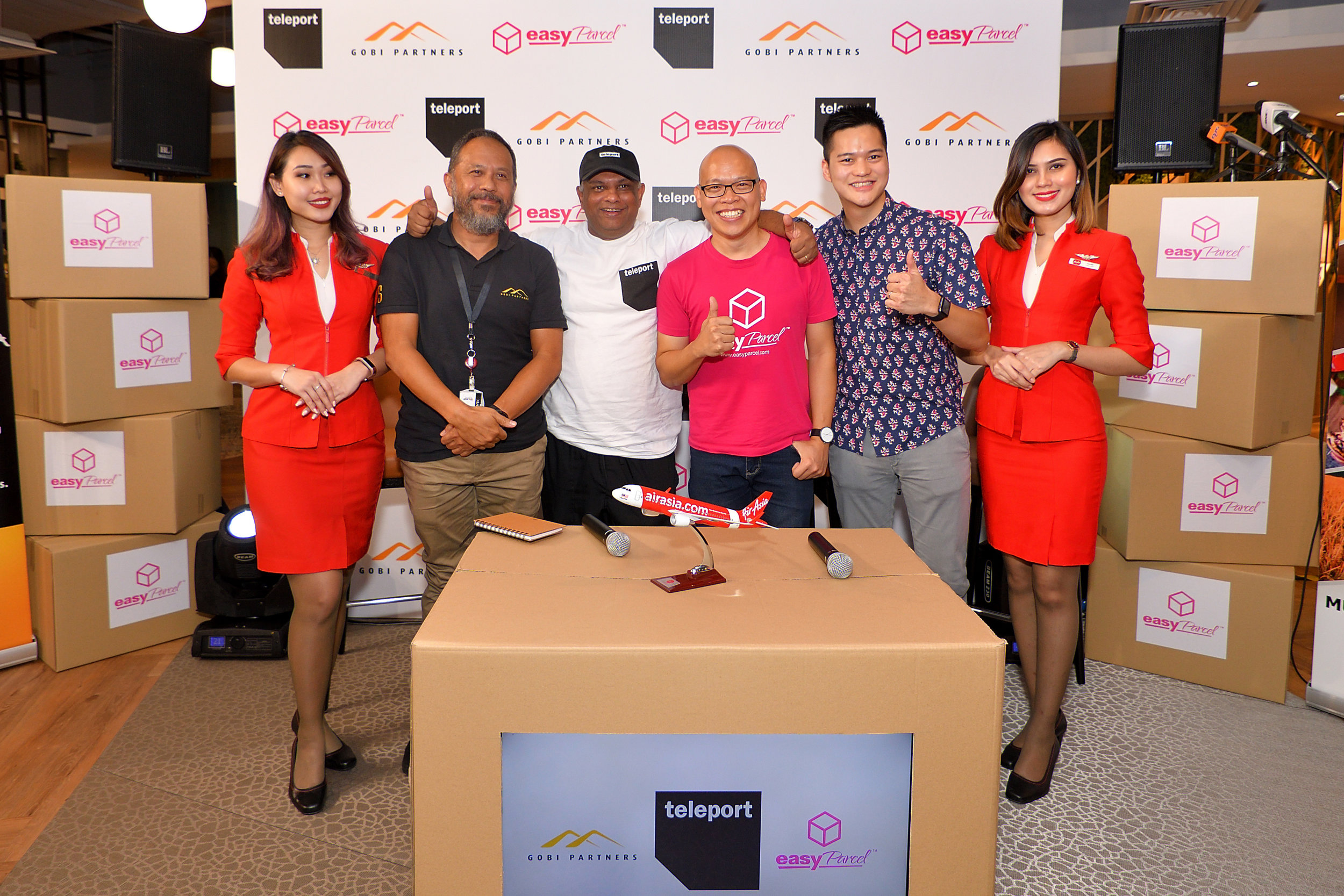Photo Caption (L-R): Managing Director Malaysia of Gobi Partners Jamaludin Bujang; CEO of AirAsia Group Tony Fernandes; Founder and CEO of EasyParcel Clarence Leong and CEO of Teleport Pete Chareonwongsak flanked by AirAsia Cabin Crew.