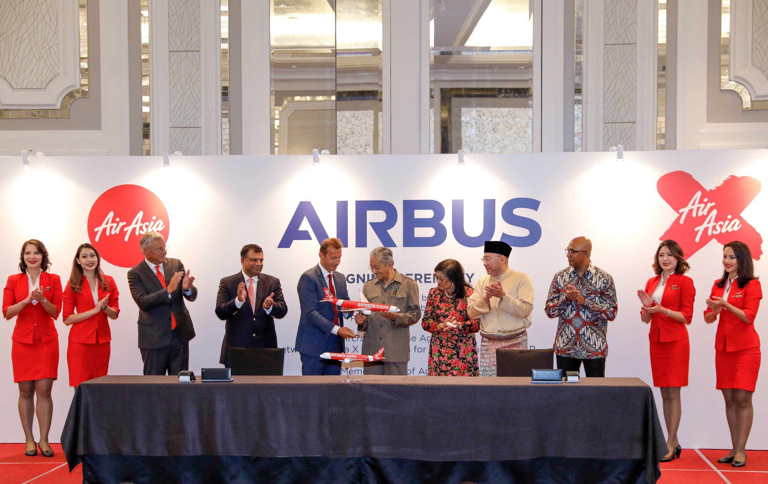 Photo caption (L-R):    Mr Christian Scherer, Airbus Chief Commercial Officer; Tan Sri Tony Fernandes, AirAsia Group CEO; Mr Guillaume Faury, Airbus CEO; YAB Tun Dr Mahathir Bin Mohamad, Prime Minister of Malaysia; Tan Sri Rafidah Aziz, Chairman AirAsia X Berhad; Datuk Kamarudin Meranun, AirAsia Group Executive Chairman; Mr Bo Lingam, AirAsia Group President (Airlines) flanked by cabin crew.