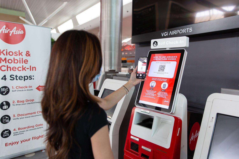 Keterangan gambar: Seorang tetamu menggunakan Kiosk Tanpa Sentuhan AirAsia.