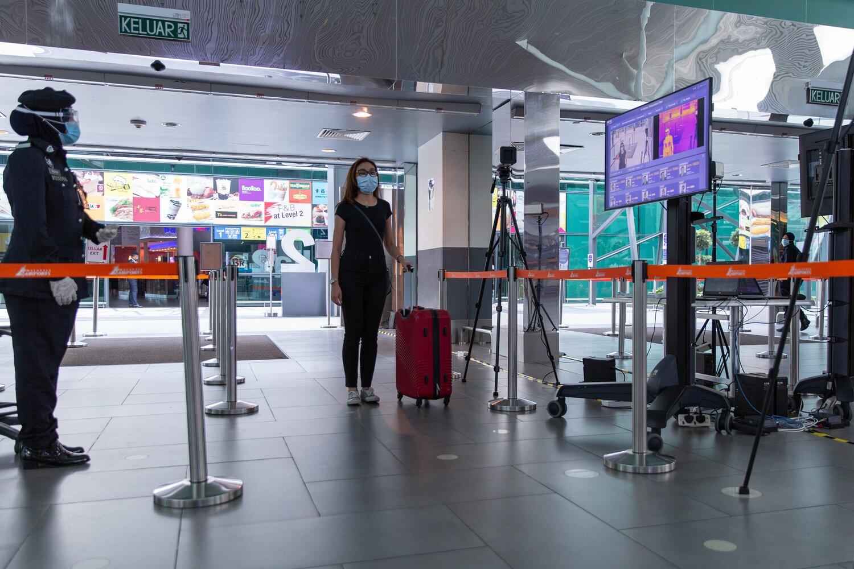 Keterangan gambar: Seorang tetamu melalui pemeriksaan suhu badan di Lapangan Terbang Antarabangsa Kuala Lumpur 2 (klia2).