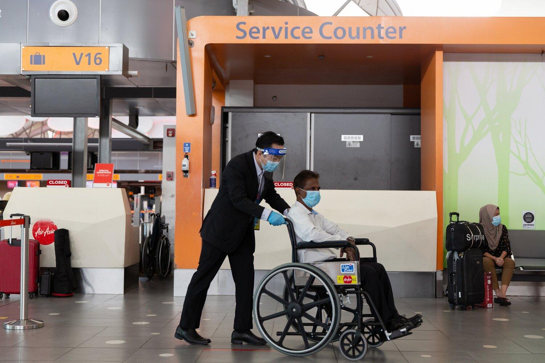 Keterangan gambar: Seorang Kakitangan Perkhidmatan Tetamu membantu membawa tetamu berkerusi roda.