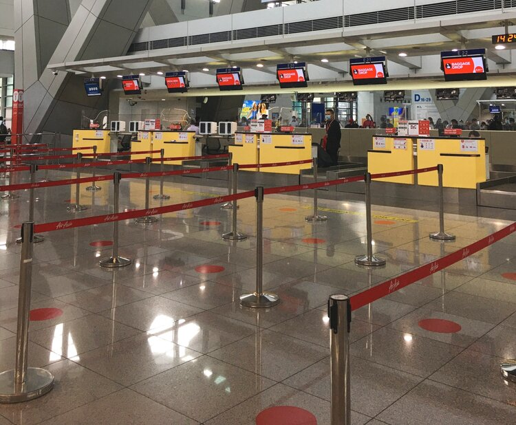 AirAsia check-in counters at NAIA Terminal 3 with physical distancing markers.