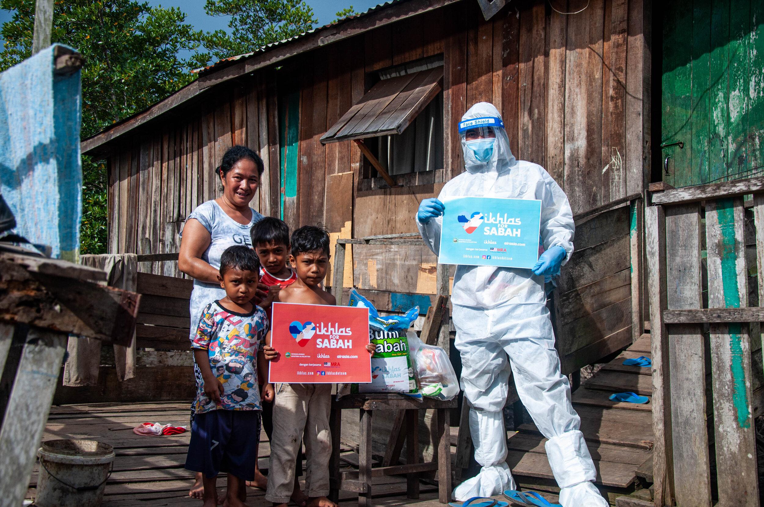 Salah seorang daripada pasukan IKHLAS mengedarkan pakej barangan keperluan harian di Sabah