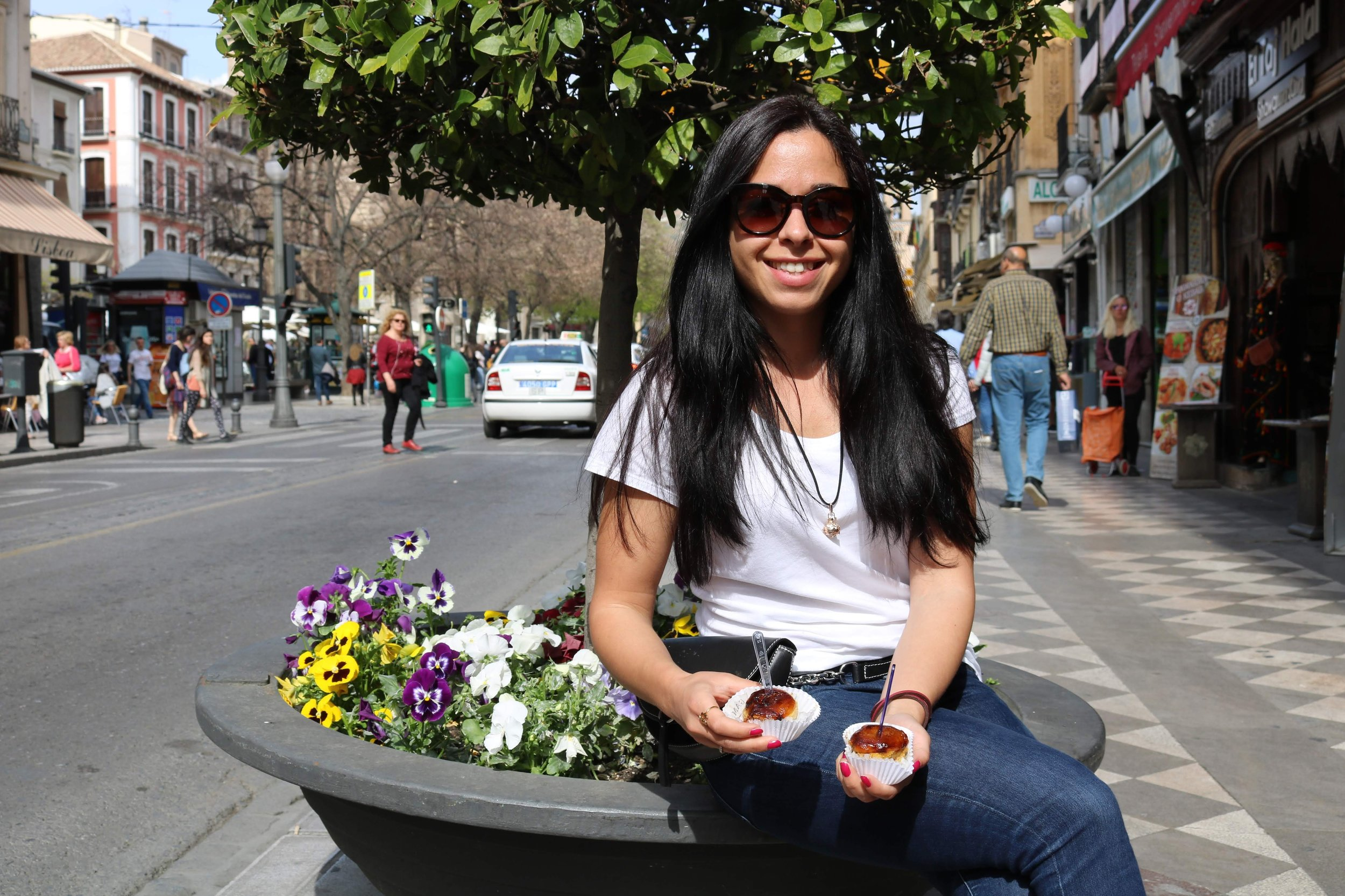 Melisa trying Piononos, the traditional pastry of Granada