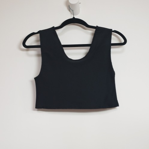 Image: A Short  black mesh binder  with Low Arms. The side seam takes up less of the vertical length than the shoulder.