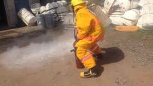 Carlyle shoots the fire extinguisher with the fire suit on.