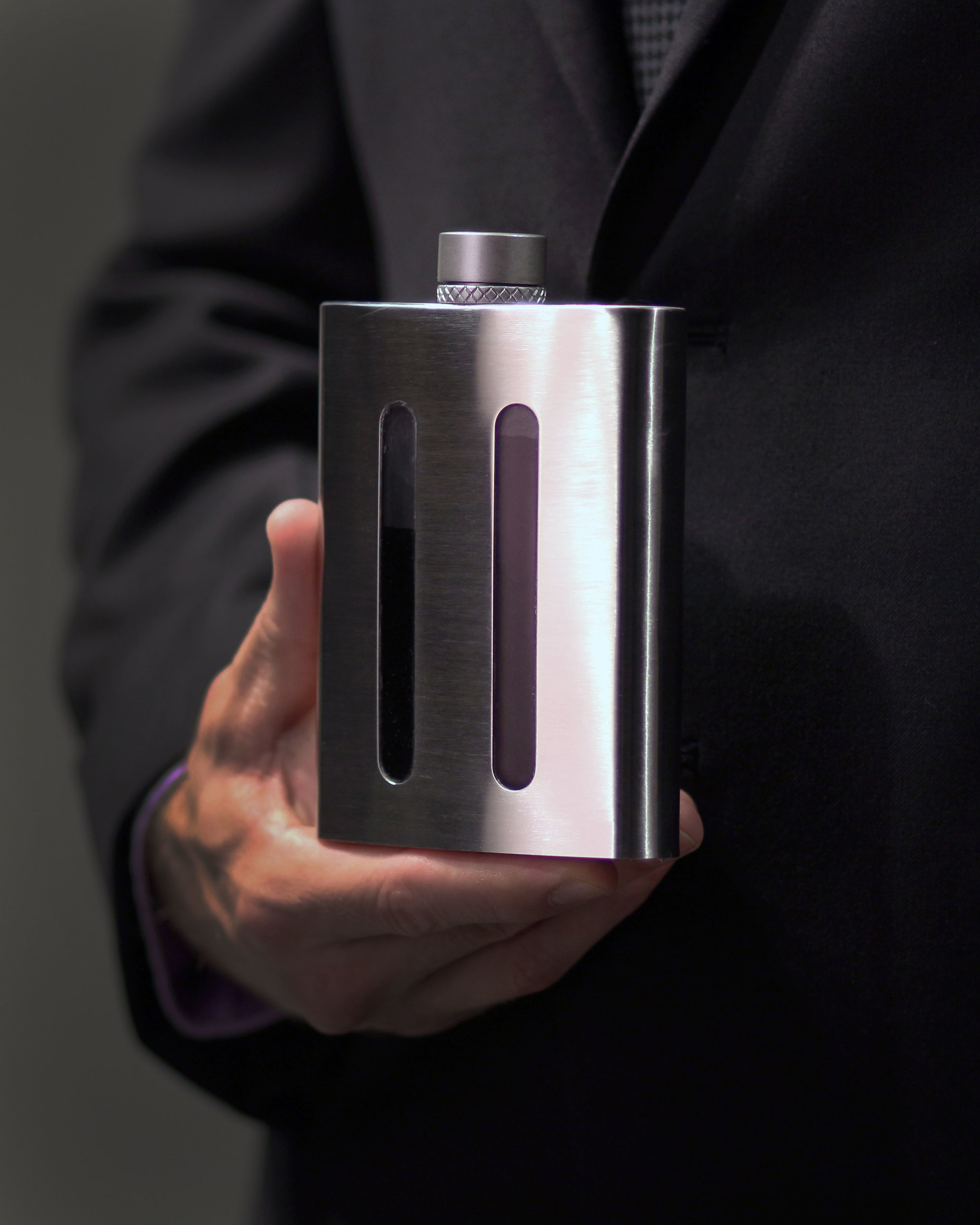man holds dividere dual chambered flask