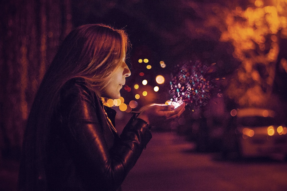 Picture taken at night of a long-haired woman wearing a leather jacket and blowing glitter out of her cupped hands.