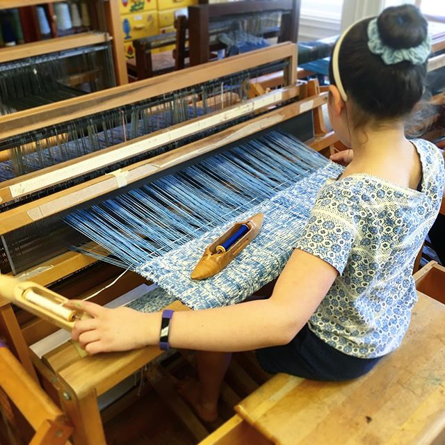 This sixth grader unintentionally color-coordinated her outfit with her weaving:  Lee's Surrender overshot pattern with a hand-dyed blue ombre cotton warp with a white chenille weft. . I still have the weaving I made in middle school on this same loom, which is still threaded with the same pattern after all these years, and it's an impressively tricky one! Wrapping up my first year teaching in this classroom and celebrating the 2019 graduation definitely stirred up lots of nostalgia with the end of the year bustle to finish up projects. . . . . .  #leessurrender #handdyed #handdyedwarp  #weavingspecialist #weavingteacher #kidsweaving #kidweavers #kidsweave #childrenweaving #childhoodweaving #weavingclass #weavingclassroom #floorloom #textileclass #textileclassroom #textileartclass #handsonlearning #progressiveeducation #peninsulaschoolweaves #weaving #handweaving #handweaver #weaver #handwoven #handwoventextiles #handmadetextiles #textiles #fiberart #fiberarts #fiberartist