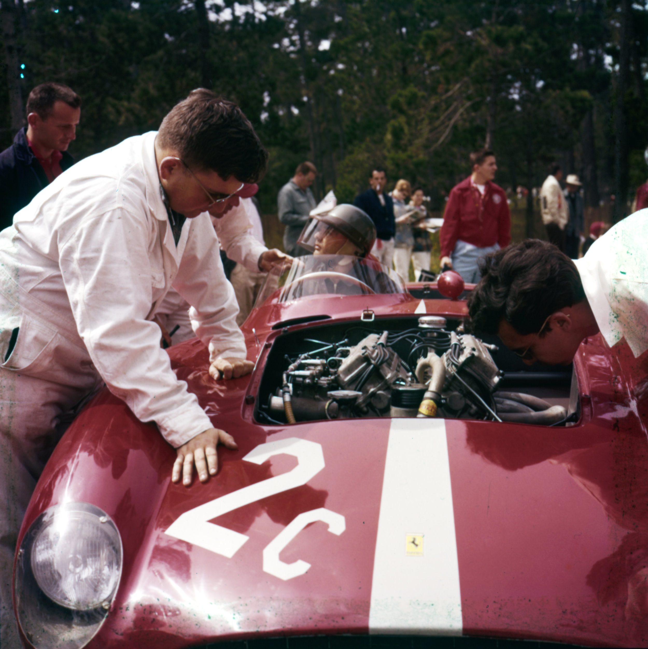 Phil Hill in a 860 Monza with hood open   Pebble Beach 1956: The mighty Ferrari 3.5-liter-four-cylinder 860 Monza of west coast Ferrari distributor John von Neumann. Phil Hill was his driver, and finished second to Carroll Shelby.