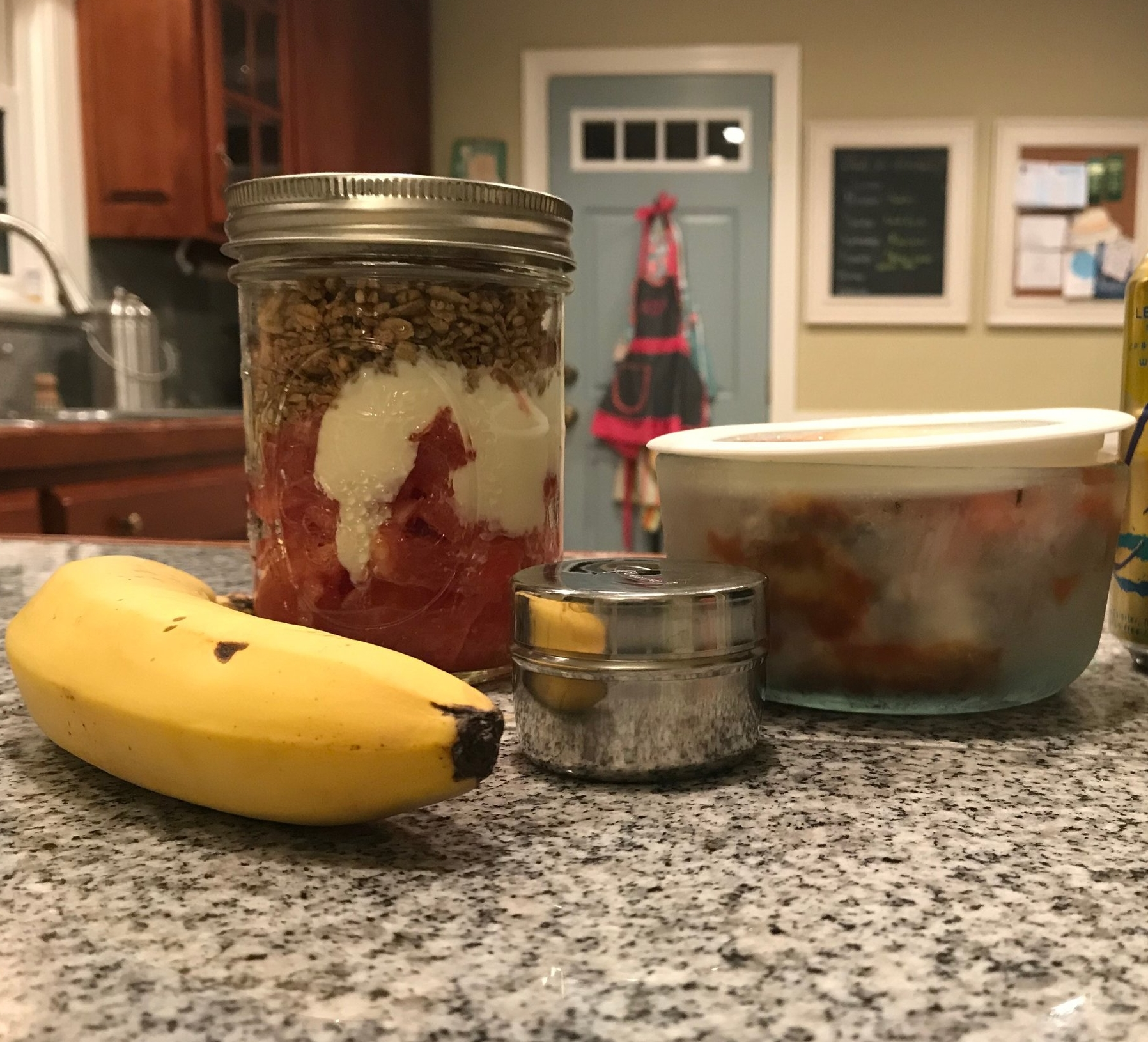 Grown up lunch and snacks for work: frozen eggplant parmesan, fruit and yogurt parfait, banana, and a little container of chocolate chips.