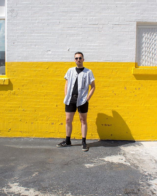 Another centered photo of me in front of a wall with my hands in my pockets and sunglasses on!