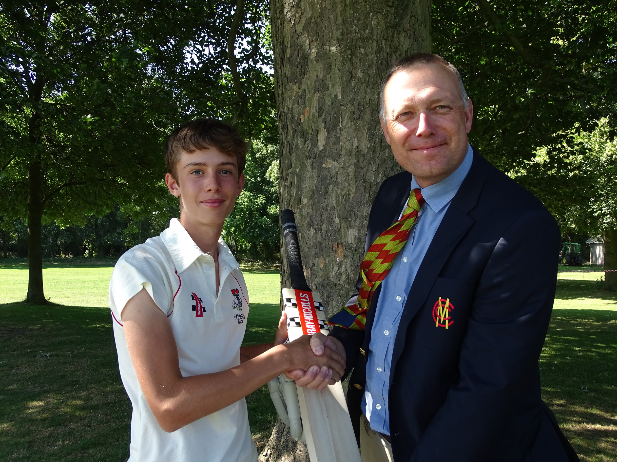 Sam receives his commemorative bat and gloves