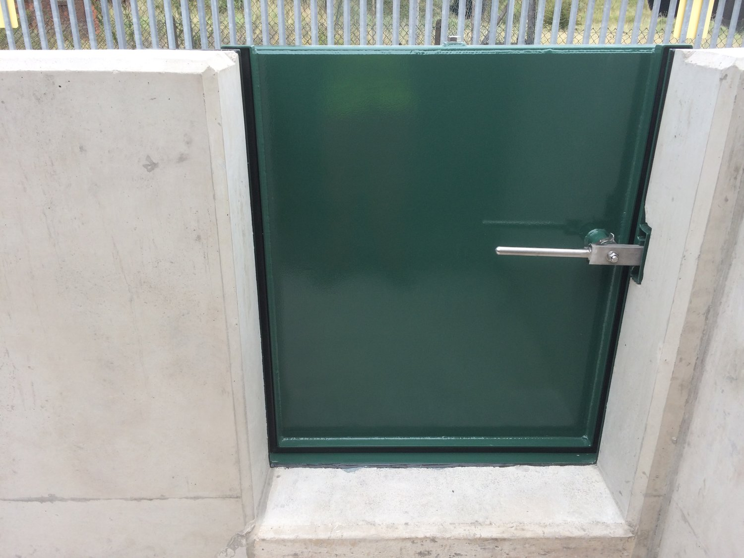 A single pedestrian flood gate built into a flood barrier wall  with a simple latch mechanism for easy operation.