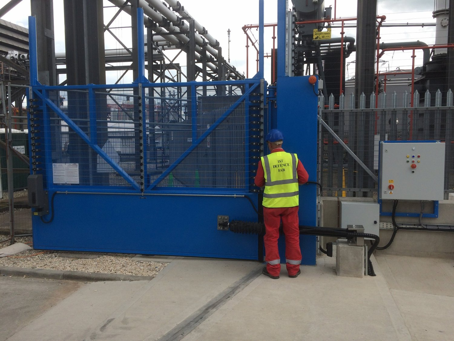 A 1stDefence Fabrications automatic  Hydraulically operated double flood gate with  security fencing. Preventing any break in the electricity  supply with the added protection against more malicious  entry into the compound.