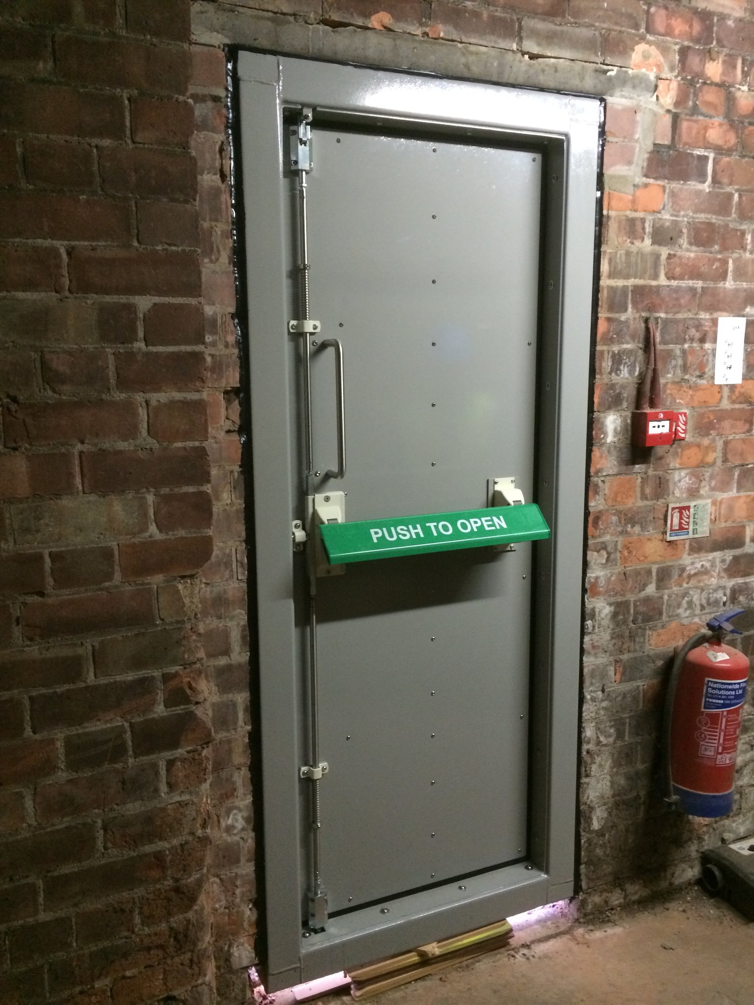 A flood door providing defence against building flooding  Whilst also being an emergency exit in case of fire.