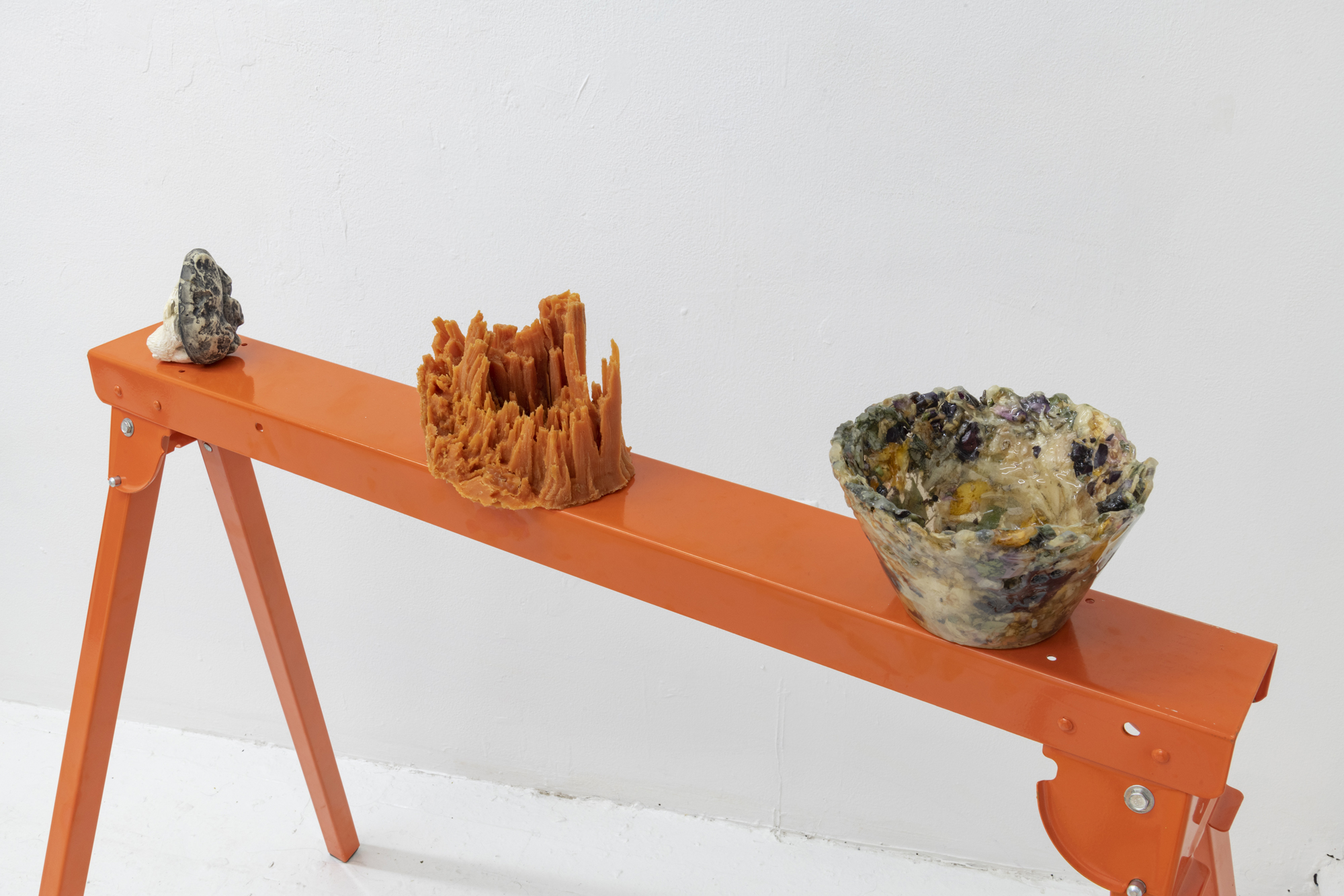 Left:   Opposite,  2018. Cast plaster, epoxy resin and hide-a-key faux rock. 4 x 3 x 3 inches.  Center :  Out of , 2018. Cast polyurethane rubber. 7.5 x 5 x 4.5 inches.  Right:   In Spite Of ,  2018. Epoxy resin and dried flowers. 4 x 7 x 7 inches.