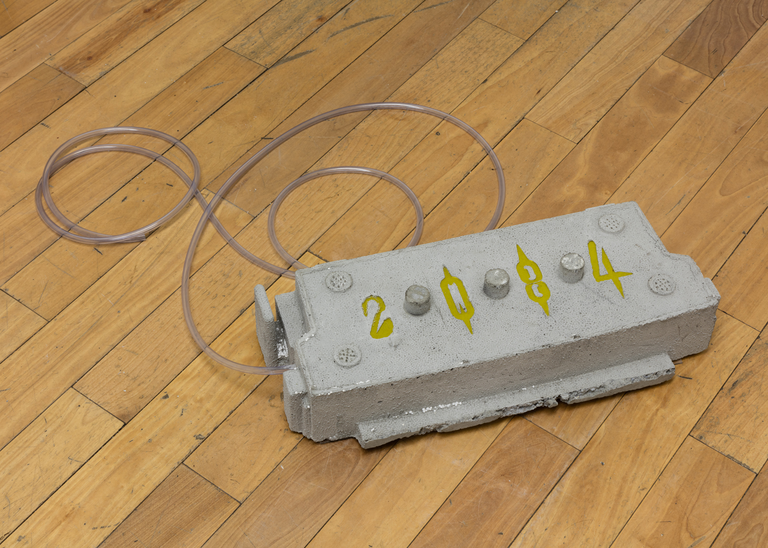 Phoebe Berglund in collaboration with Arkadiy Ryabin,  2084,  2019. Concrete, rebar, plexiglass, vinyl tubing. 5 x 22 x 8 inches.
