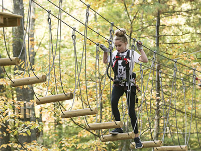 Girl-climbing-on-a-bridge-obstacle-course-in-the-trees-at-TreeTop-Adventures-in-Canton.jpg