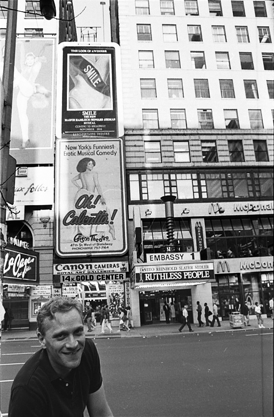 Howard beneath a  Smile poster on Broadway