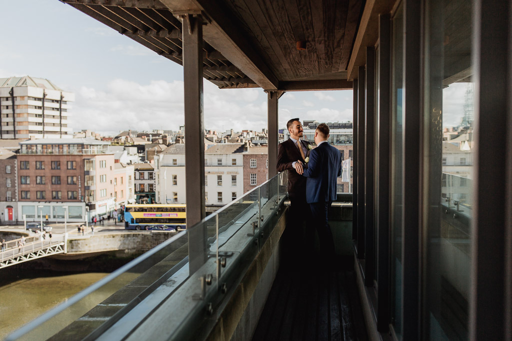 wedding photographer dublin. two grooms at the balcony of the morrison hotel
