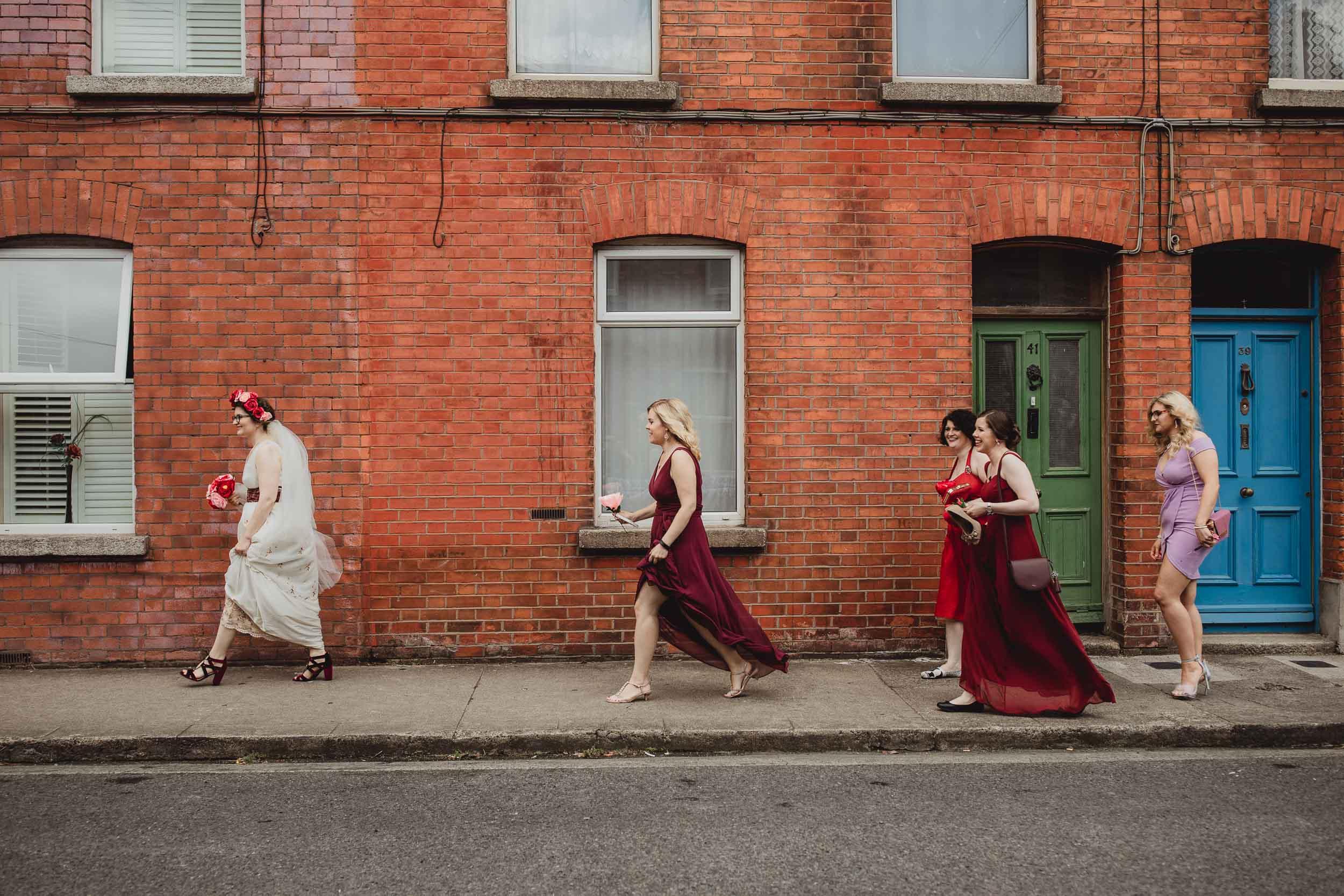 wedding photographer dublin.bride and bridesmaids walking on dublin street.