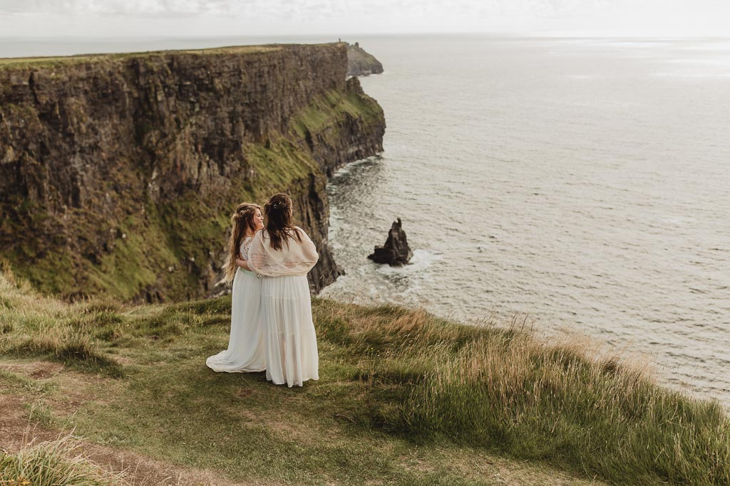 Cliffs of Moher wedding. Two brides holding each other.