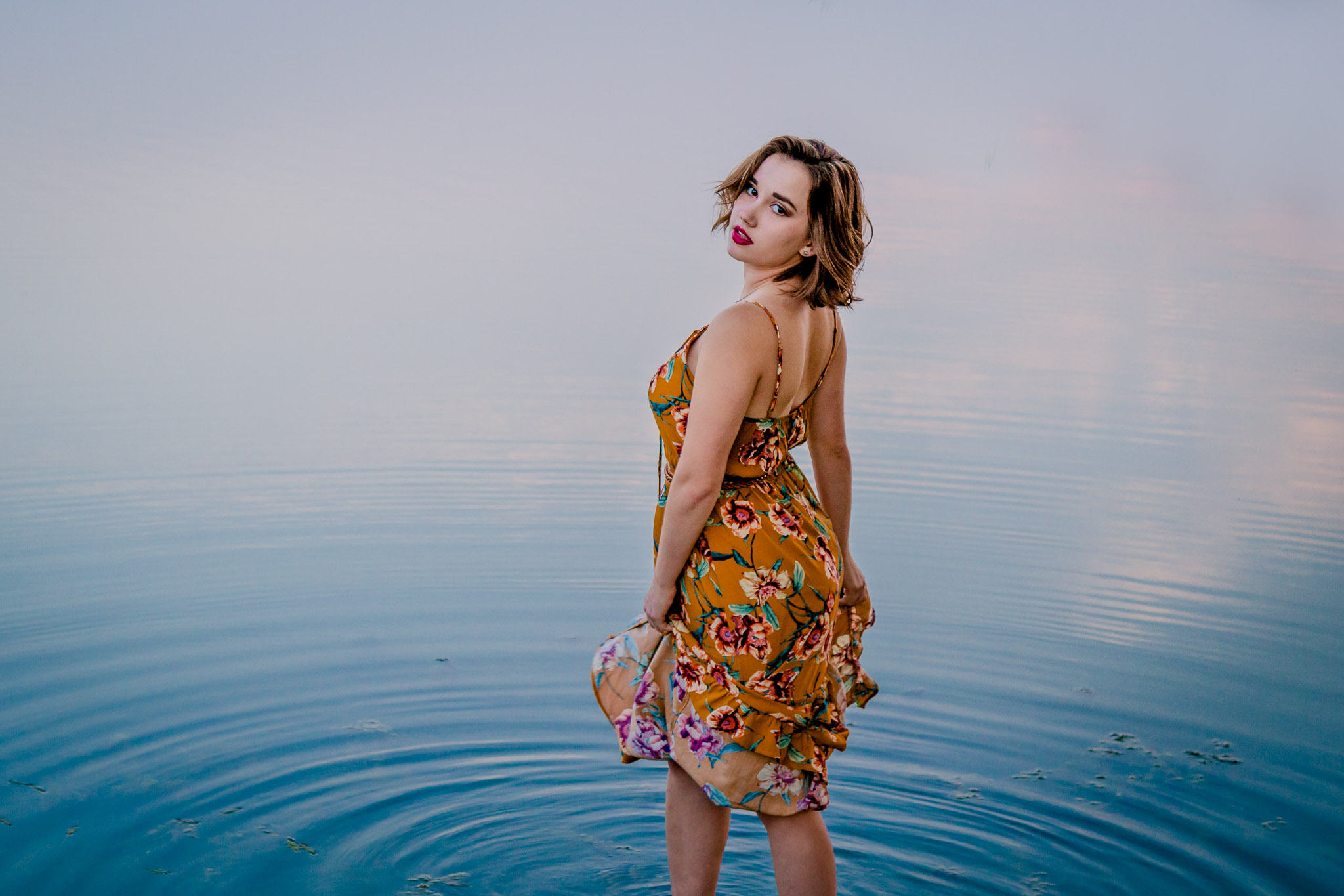 senior photo in the water at sunset