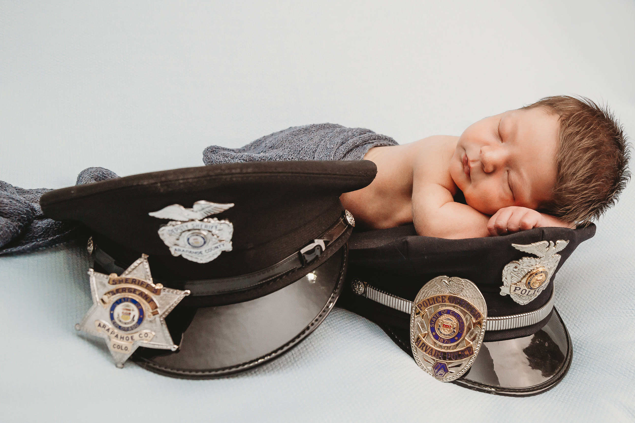 baby on police hats with badges