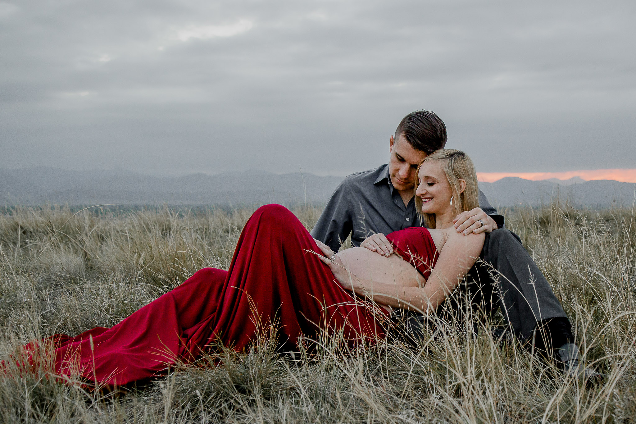 Romantic-Maternity-Couple-Field-Laying-Down-Red-Dress-Littleton.jpg