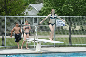 Swimmer on the diving board at the outdoor swimming pool.