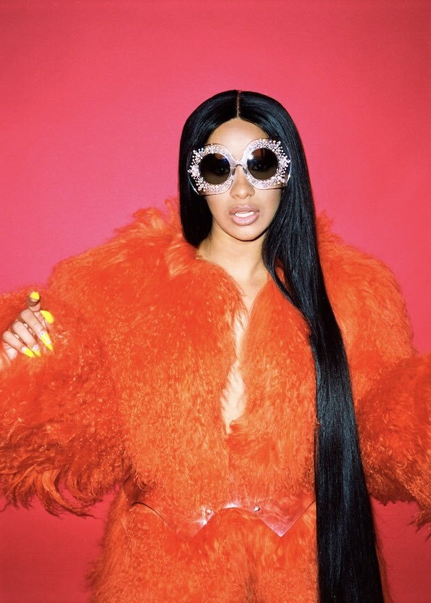 Cardi B posed for Paper Magazine wearing a bold orange fur by Jennifer Le and embellished Docle & Gabbana sunglasses.