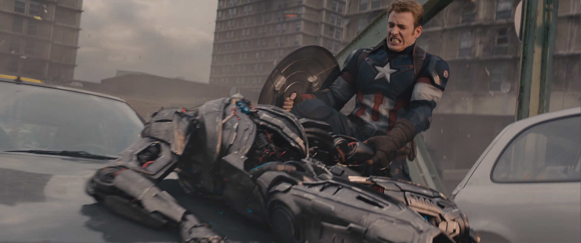 In this shot I had to remove a very big person wearing a mocap suit. I had to rebuild the background cars using projections and the foreground car using parts of a CG car. I also had to rebuild many parts of Captain America using patches and projections, and CG body parts. I added different layers of blowing dust and debris and added the burning marks on the buildings in the background. I also did sky replacement and added sparks and flying pieces of the Sub-Ultron's arm as it ge's ripped apart.