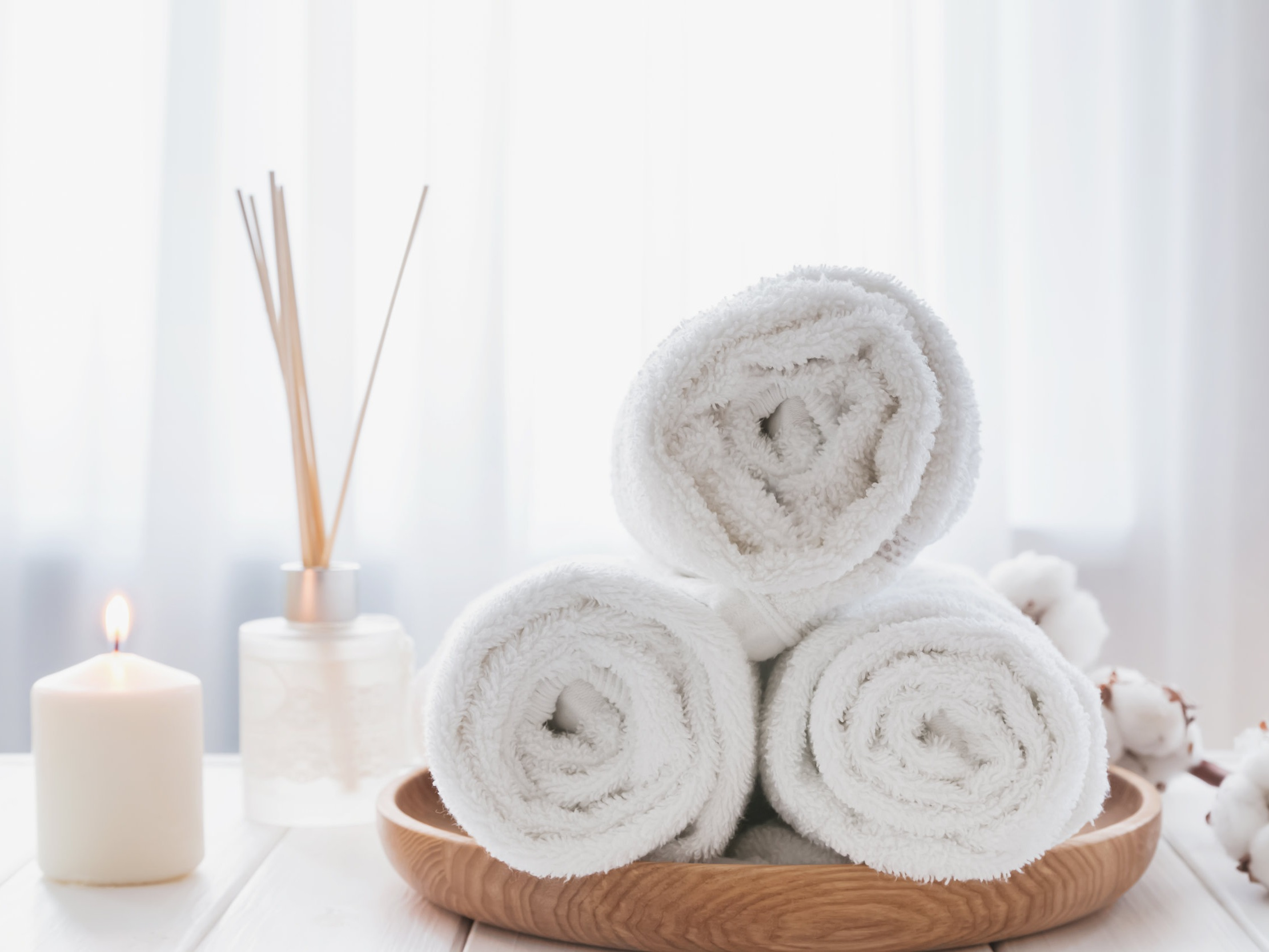 Canva - Clean white towels on the wooden tray, candle and aroma diffuser..jpg