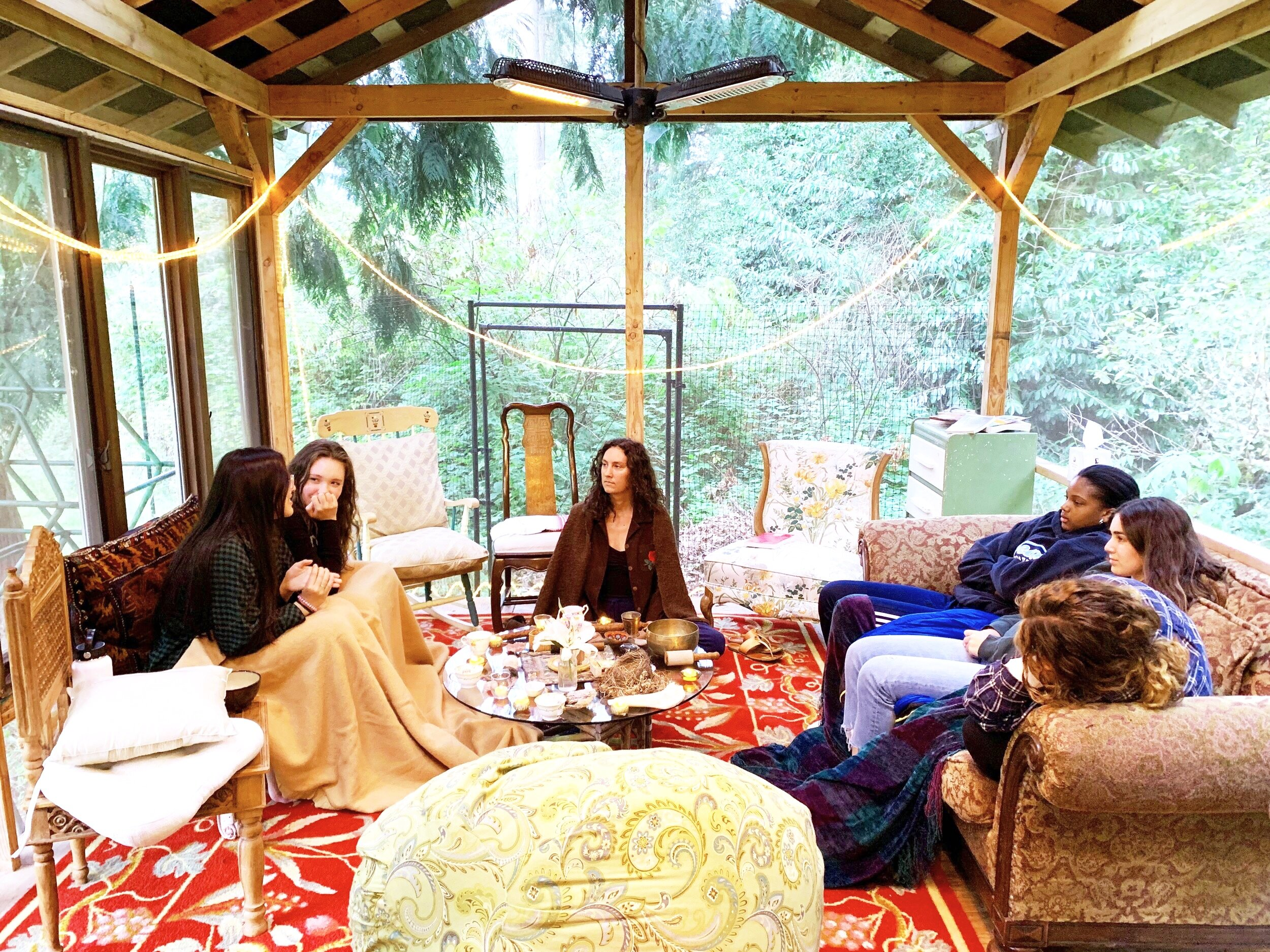 """Teen circles can happen wherever you want to meet up and sit in circle. They can take place on a nature hike, in a school room, in a church or temple — anywhere you can create a private space and carve out time. Each year, the Seattle Girls Circle holds a summer sleepover in a little cabin in the woods. We set up a central table full of meaningful objects: candles, shells, bones, precious stones, feathers, bowls of water and Earth, and Tibetan singing bowls. These """"things"""" honor and symbolize that we're establishing a sacred space and time — setting a symbolic boundary to distinguish that this will not be a place for the """"normal"""" way we interact with each other, the normal conversations. Instead we are establishing that this will be a time for a deeper form of listening and sharing of our real selves, vulnerable selves, the selves in us that need to be seen and heard in order to grow and become even more our true selves in the world. In this safe space, we can talk about the hard issues — all the isms we experience as individuals in this world and grow our capacities for compassion for each other and ourselves. We deeply inform each other."""