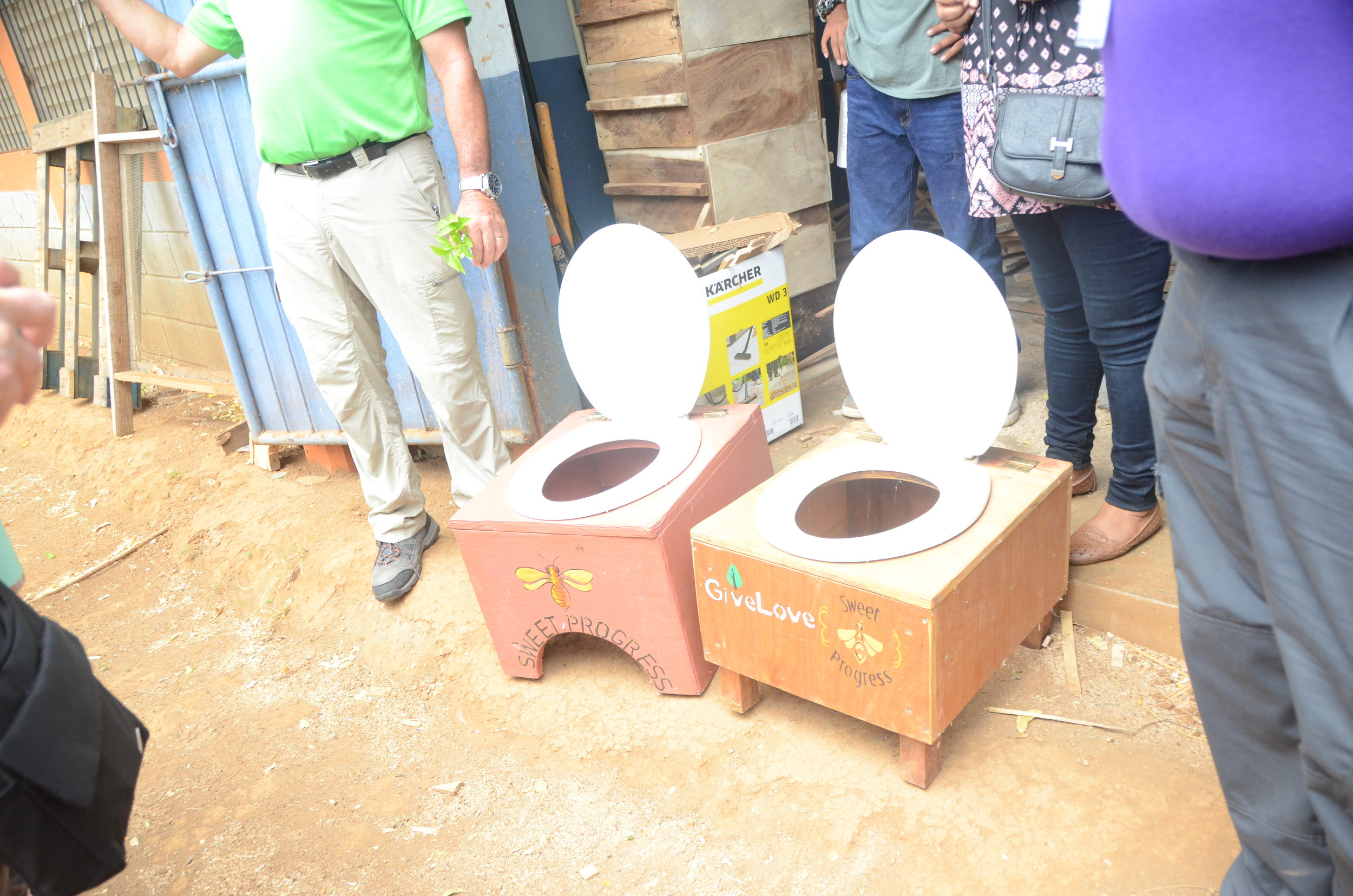 They are also making these toilets from the boxes. They use the boxes in step one to making things, after they master making things from the boxes they move on to wood. The toilet on your right is wooden. A person uses this toilet, cat style. with a bucket full of saw dust underneath, it's a dry toilet.