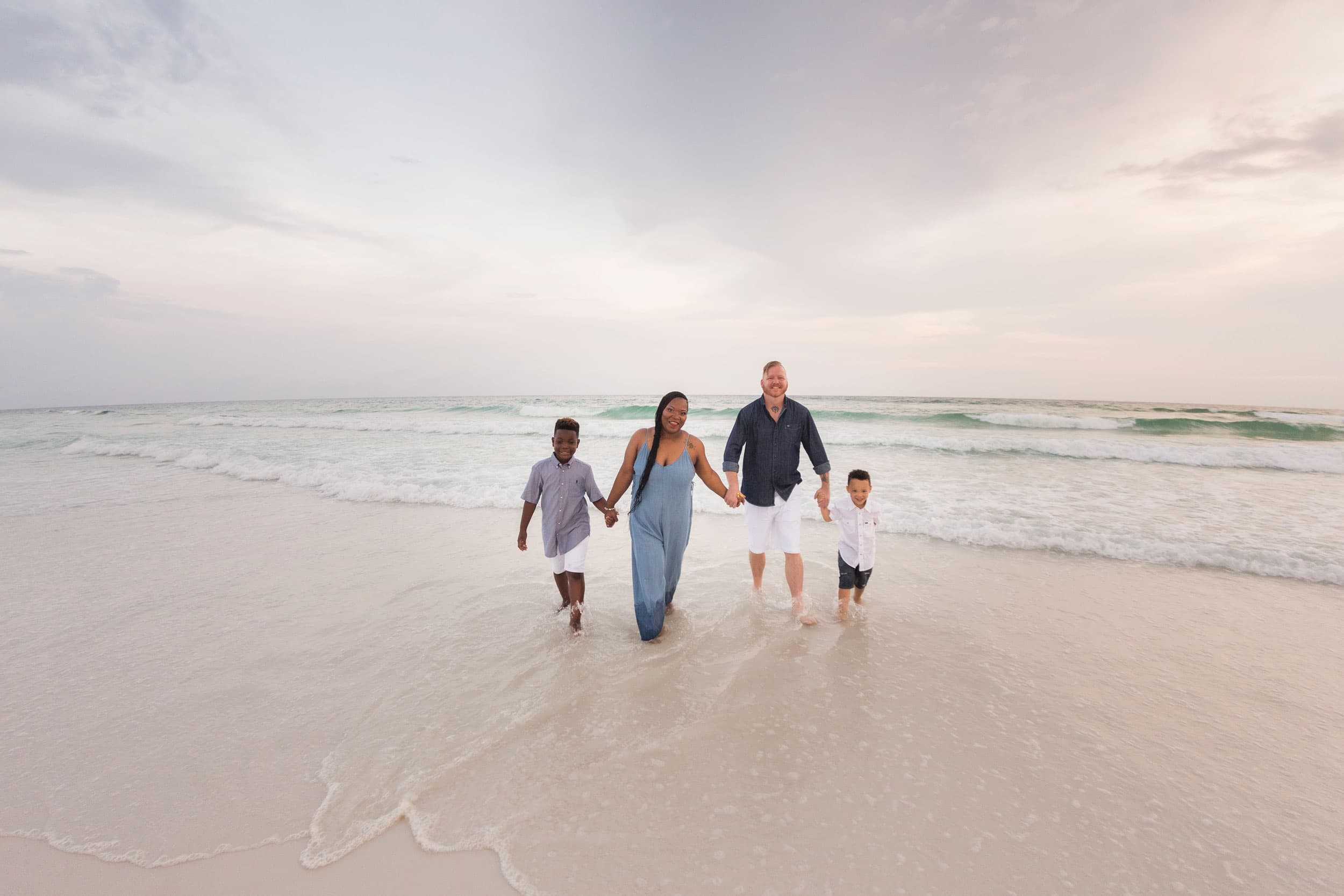 Vacationing parents and children walk during beach session