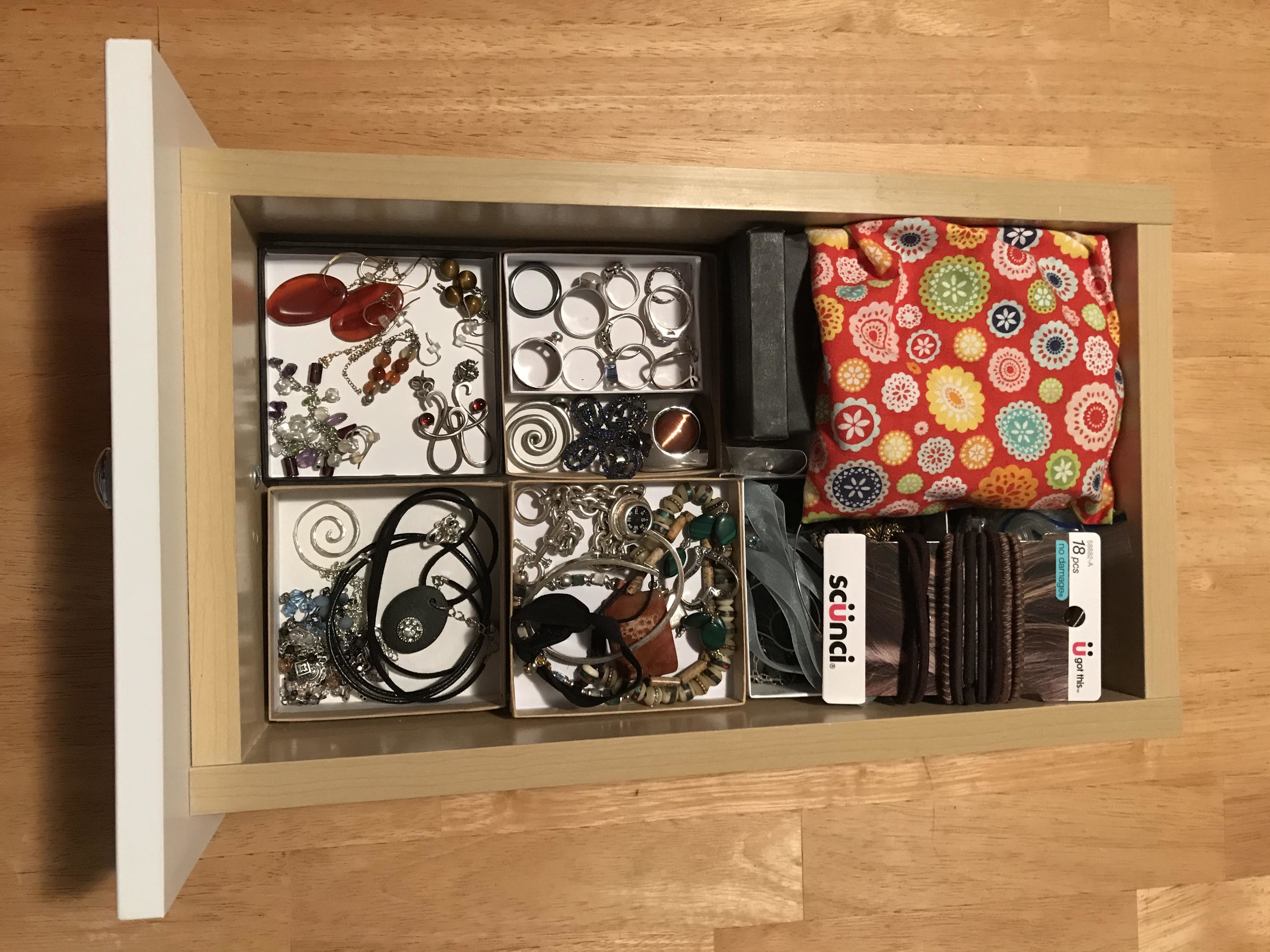 There are all kinds of ways to organize jewelry. Sometimes super simple is the ticket. One small drawer with layered boxes.