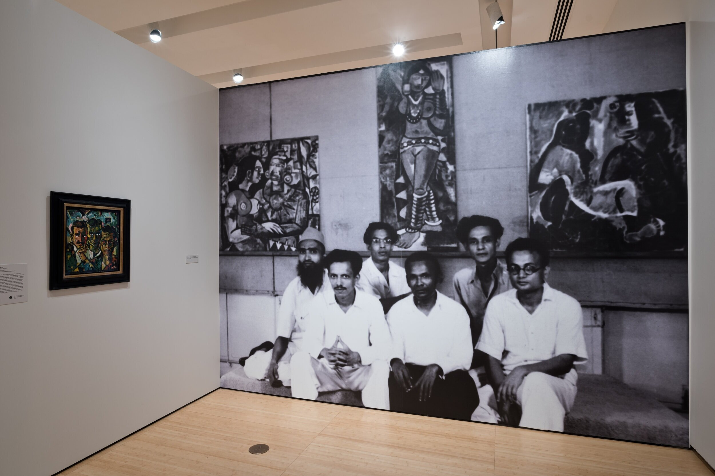 """Installation view of exhibition """"The Progressive Revolution: Modern Art for a New India"""" at Asia Society Museum, New York, 2018. Photograph, Perry Hu; courtesy Asia Society Museum. S.H. Raza.  Untitled , ca. 1940s, Jane and Kito de Boer Collection. Progressive Artists Group, Bombay, 1949. Image courtesy The Raza Archives, The Raza Foundation, New Delhi, India.  In Image (L-R), Row 1: F.N.Souza, K.H. Ara, H.A. Gade; Row 2: M.F. Hussain, S.K.Bakre, S.H. Raza"""