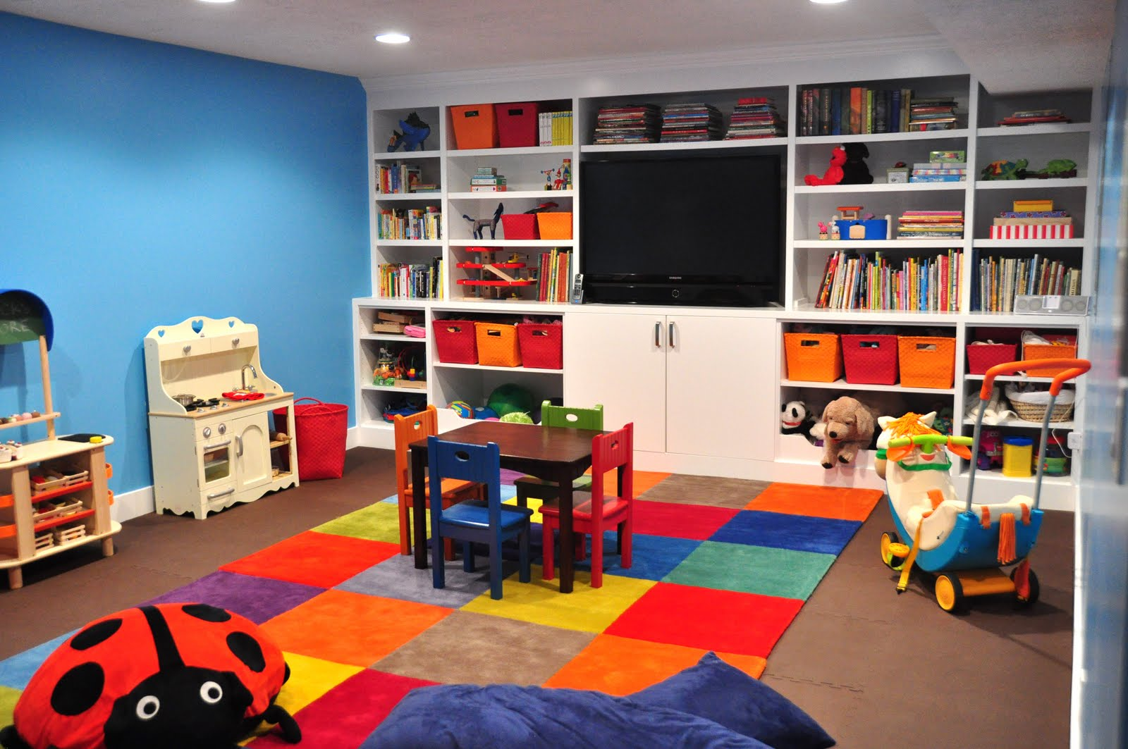 patchwork-rug-of-bright-multicolored-squares-built-in-storage-and-flatscreen-TV.jpg