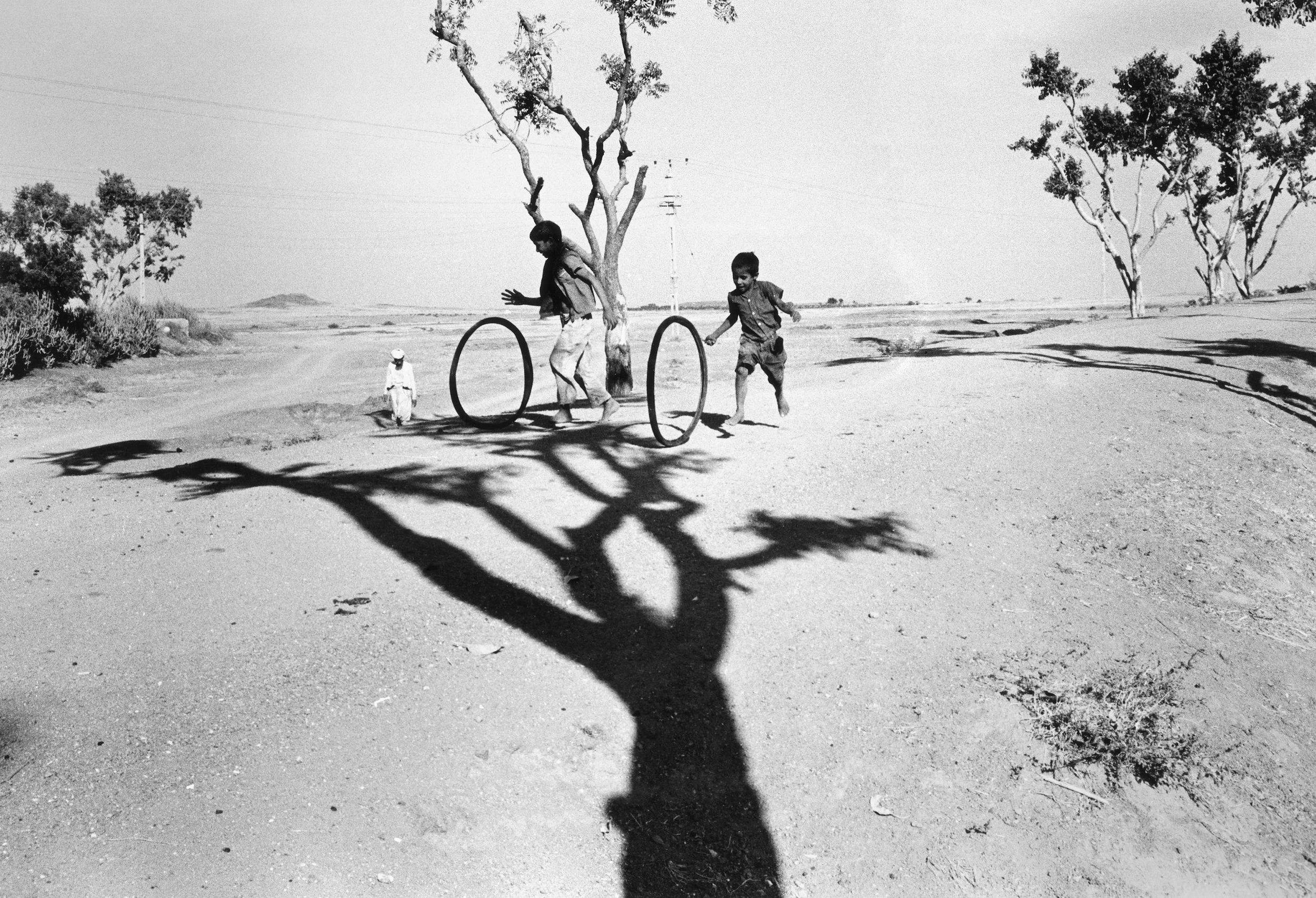 Bhupendra Karia,  Boys playing hoops in landscape, Gonda l, 1969