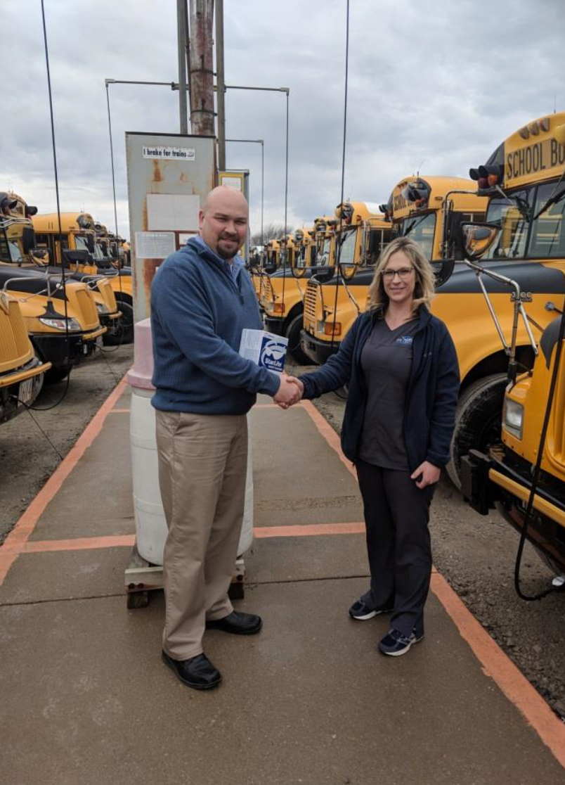 Nicole Heyduk handing the sunglasses to Justin Eilrich, Transportation Manager at Fremont City Schools
