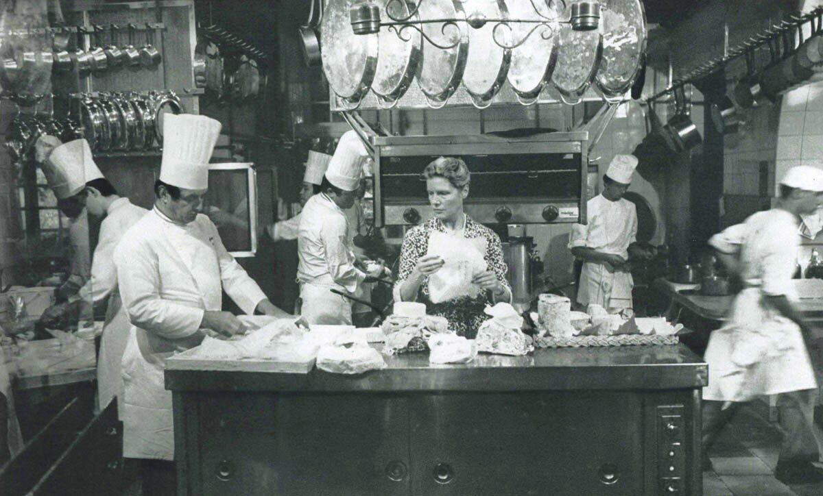 The view of Paul Bocuse's kitchen including Madame Bocuse preparing the daily cheese tray. Photograph: © Anthony Blake