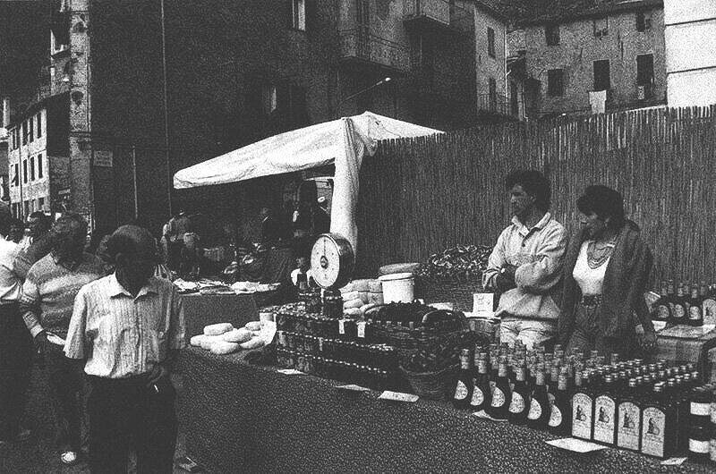 Vendors selling homemade sauces in jars in a Ligurian market.