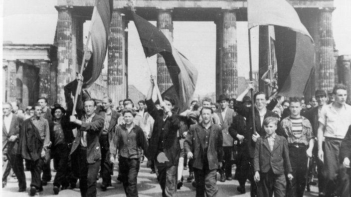 Workers march through the Brandenburg Gate, East Berlin