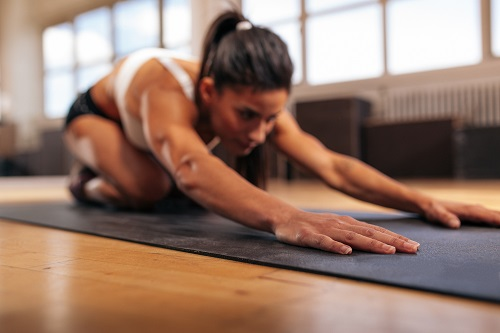 female-performing-yoga-on-exercise-mat-at-gym-PGWBCVD.jpg