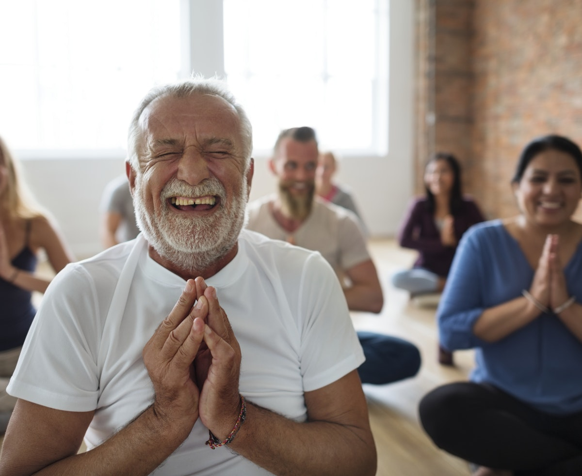 Older man doing yoga, meditation and laughing