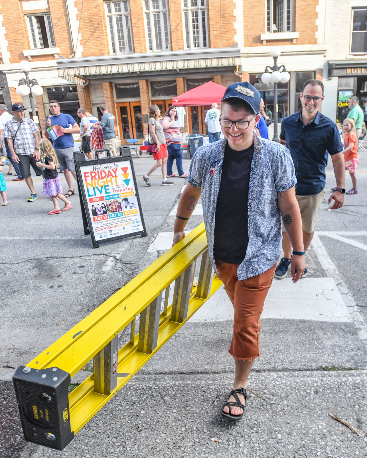 The Downtown Rutland Partnership's Streetscape Coordinator, Jess Novak, and Steve Peters, Executive Director, move a ladder to hang extension cords at Friday Night Live 2018.   Photo credit: Robert Layman / Rutland Herald