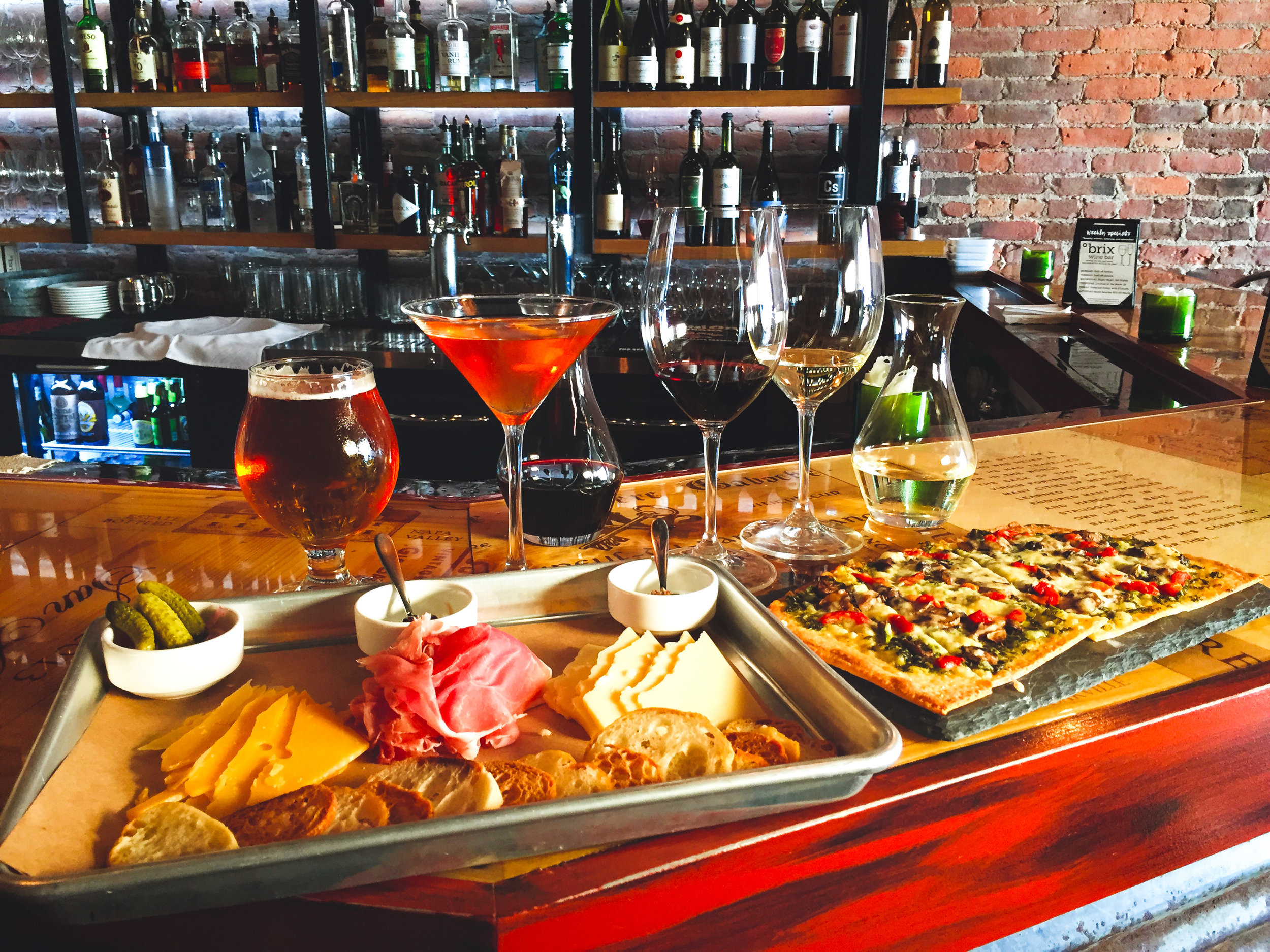 A charcuterie and cheese board, a flat bread pizza and drink options at Brix Bistro in Downtown Rutland, Vermont.
